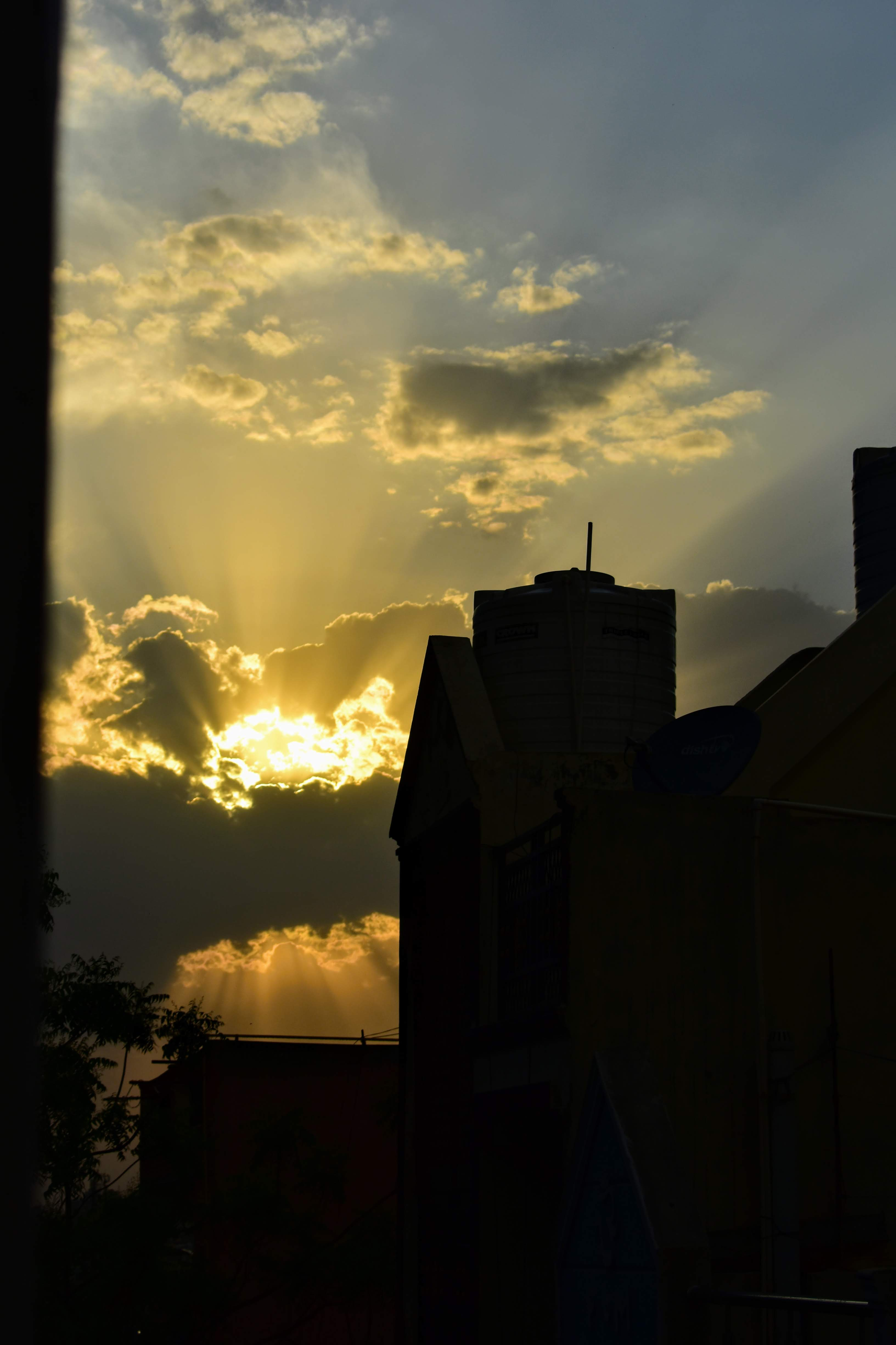 Aesthetic Blasphemy | Image of the sun's golden rays emerging from behind clouds on an evening