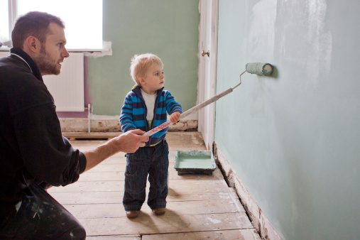 Father and son paint wall together